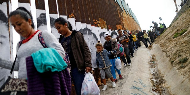 Members of a caravan from Central America walk next to the border fence between Mexico and the U.S., before a gathering in a park and prior to preparations for an asylum request in the U.S., in Tijuana, Mexico April 29, 2018.