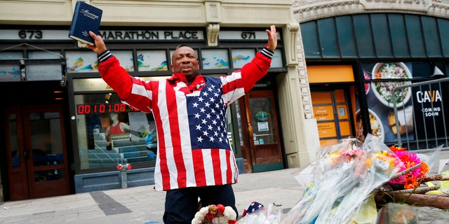 Cristopher Nzenwa, of Boston, prays at the site of the first explosion during the 2013 Boston Marathon, Sunday, April 15, 2018, in Boston.