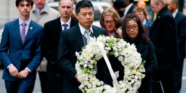 The father of Lingzi Lu, Jun Lu, foreground left, and her aunt Helen Zhao, foreground right, carry a wreath ahead of the family of Martin Richard, background from left, Henry, Bill, Denise and Jane, partially hidden, during a ceremony at the site where Martin Richard and Lingzi Lu were killed in the second explosion at the 2013 Boston Marathon, Sunday, April 15, 2018, in Boston.
