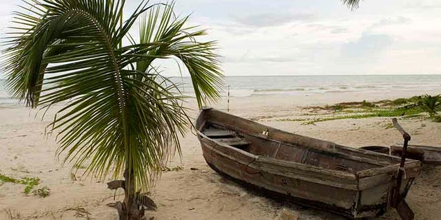 A boat, which members of the Mexican Navy and local villagers say was abandoned by people smugglers transporting Cubans to the Yucatan peninsula, lies on a beach in the community of Cuyo on the Yucatan peninsula October 10, 2007. Record numbers of Cubans are now using Mexico as their route to the U.S. instead of the Straits of Florida. Cubans, unlike other Latino migrants, just have to request political asylum to be allowed to enter the U.S. legally. Picture taken October 10, 2007. REUTERS/Victor Ruiz (MEXICO) - RTR1UTGY