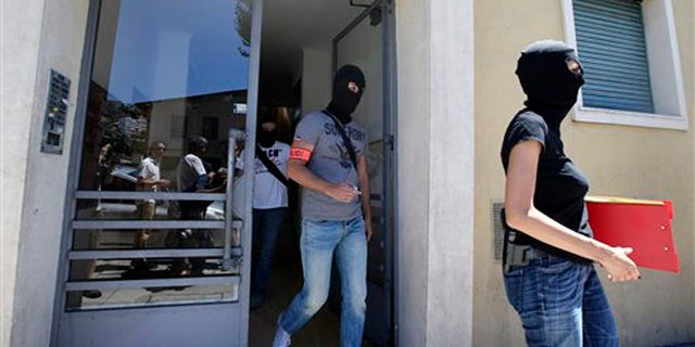 July 16: French hooded police officers leave the building where Bouhlel lived in Nice.
