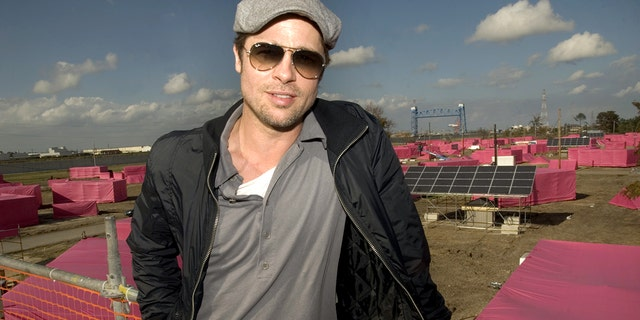 """Brad Pitt is pictured before pink stand-in structures (background) where 150 ecologically sustainable homes are to be built 03 December 2007 in the Lower 9th Ward of New Orleans, Louisiana. Pitt is spending $12 million with his """"Make It Right Project"""" to build the homes where levees broke and floodwater pushed houses from their foundations during Hurricane Katrina in August 2005."""