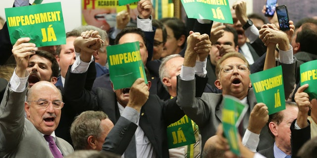 """April 11, 2016: As they hold a sign reading """"impeachment now"""" opposition lawmakers celebrate after the results of the voting at a congressional committee in Brasilia, Brazil"""