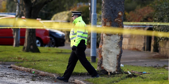 A police officer walks behind crime scene tape at the scene where a stolen car crashed into a tree, leaving 5 people dead, including 3 children, in Leeds, Britain, November 26, 2017.