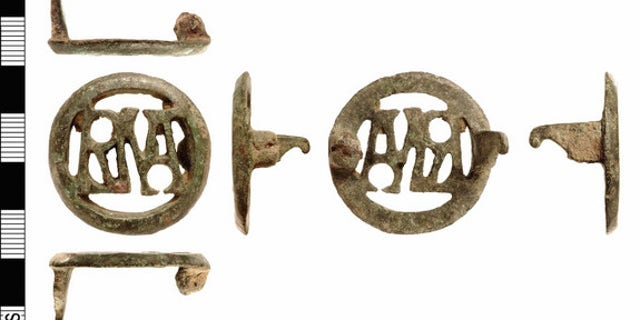 """This copper brooch contains the letters """"RMA,"""" which when read from left to right forms the monogram for """"Roma"""" the city of Rome and its god. Read from right to left it forms the monogram for """"Amor"""" the Latin name for Cupid, the god of Love. Th"""