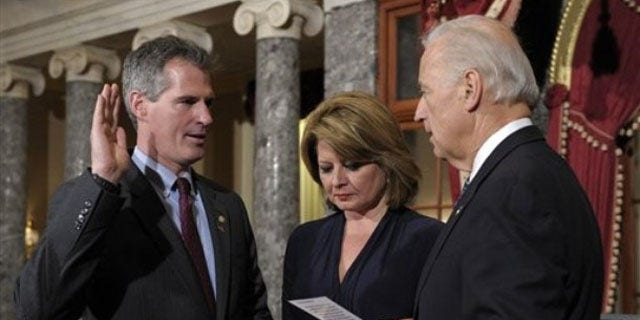 In this Feb. 4 photo, Vice President Biden, right, reenacts the swearing in of Sen. Scott Brown, left, as Brown's wife Gail Huff holds the family bibles in the Old Senate Chamber. (AP Photo)