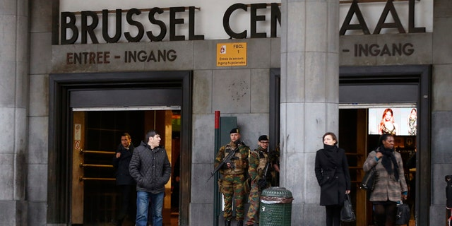 """Commuters walk past soldiers on duty at Brussels Central Station as they return to work after the easter holidays in Brussels, Tuesday, March, 29, 2016. The mayor of Brussels, holding special meetings in Paris after deadly attacks on his city, says the European Union's capital can never go back to """"normal"""" again.  Yvan Mayeur met with Paris Mayor Anne Hidalgo in the French capital's neo-Renaissance city hall Tuesday for discussions on how Paris reacted to the November attacks.(AP Photo/Alastair Grant)"""