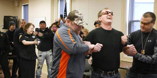 Alyssa Elkins, 16, uses a Taser on Newark Police Sgt. Doug Bline at the Newark, Ohio Police headquarters on Sunday, Jan. 29, 2017. Police helped Elkins, a teenage leukemia patient cross off a bucket-list item that was seriously shocking; she wanted to use a stun gun on someone. (Alan Miller/The Columbus Dispatch via AP)