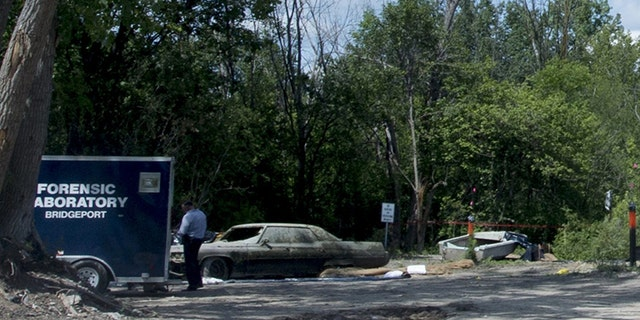 In this Aug. 15, 2017 photo, Michigan State Police Forensic Laboratory detectives investigate the scene where a car containing a body was discovered submerged in a pond in Buena Vista Township, Mich. The discovery of the Buick sedan was made by workers removing barrels from the pond. (Jacob Hamilton/The Bay City Times via AP)