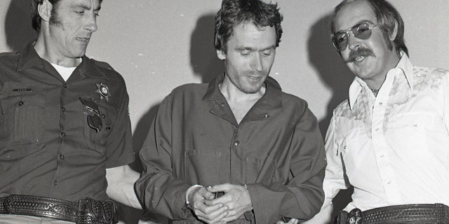 In this 1977 photo, serial killer Ted Bundy, center, is escorted out of court in Pitkin County, Colo.