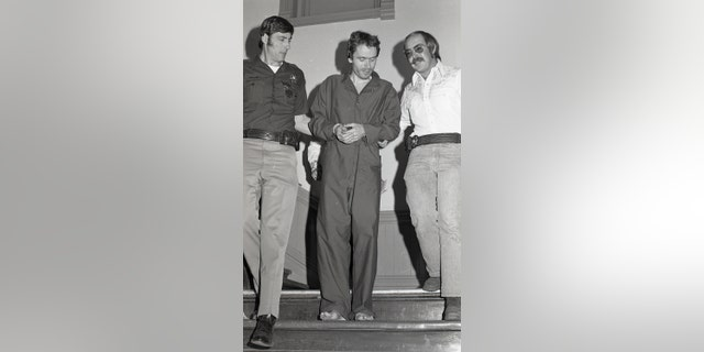 In this 1977 photo, serial killer Ted Bundy is escorted out of court in Pitkin County, Colo.