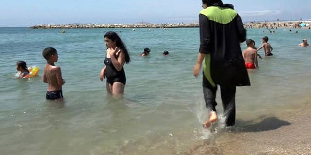 FILE -- In this Aug. 4 2016 photo made from video, Nissrine Samali, 20, gets into the sea wearing a burkini, a wetsuit-like garment that also covers the head, in Marseille, southern France.