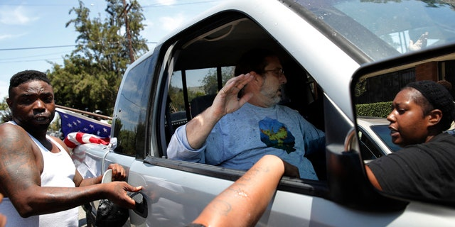 People in a counter-protest try to open the door of a pickup truck occupied by two men outside the Los Angeles office of U.S. Rep. Maxine Waters, Thursday, July 19, 2018, in Los Angeles.