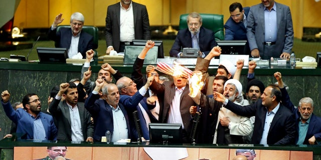 Iranian lawmakers celebrate as they burn a paper American flag.