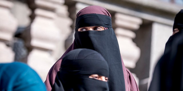 Women wearing the islamic veil niqab stand outside the Danish Parliament, at Christiansborg Castle, in Copenhagen, Denmark, Thursday May 31. 2018.