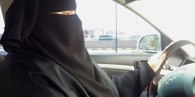 A woman wearing a burka, behind the wheel of a car.
