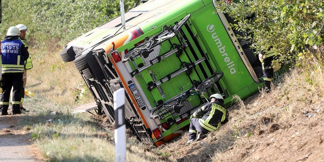 A bus sits beside the Autobahn A 19 in Linstow near Rostock, northern Germany, Friday, Aug. 17, 2018, after it was driven into a ditch and turned over.
