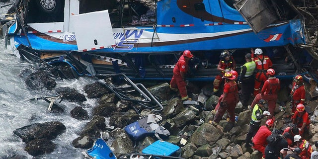 In this photo provided by the government news agency Andina, firemen recover bodies from a bus that fell off a cliff after it was hit by a tractor-trailer rig in Pasamayo, Peru, on Tuesday. Peruvian officials said at least 48 people died, and that there were more than 50 people on the bus.