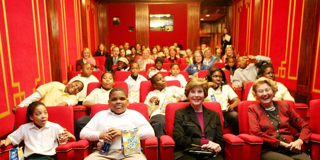 """Students and their mentors from Everybody Wins! DC, a community-based mentoring program, join U.S. first lady Laura Bush (front, 2nd R) and her mother Jenna Welch (front R) to watch C.S. Lewis' """"The Chronicles of Narnia: The Lion, The Witch, and The Wardrobe"""" in the White House Theater, December 2005."""