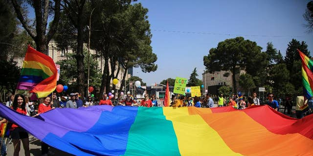 Participants of the Gay Pride Parade hold a rainbow flag during a rally held without any disturbances, while the country's political opposition prepared for an unrelated national protest in the capital, in Tirana, Albania, in 2017.