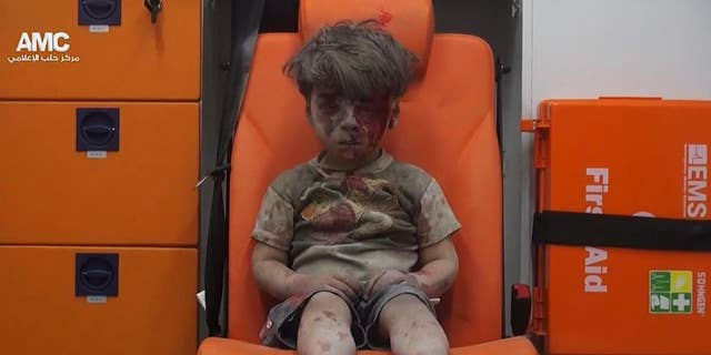 In this Aug. 17, 2016 file frame grab taken from video provided by the Syrian anti-government activist group Aleppo Media Center (AMC), 5-year-old Omran Daqneesh sits in an ambulance after being pulled out of a building hit by an airstrike in Aleppo, Syria.