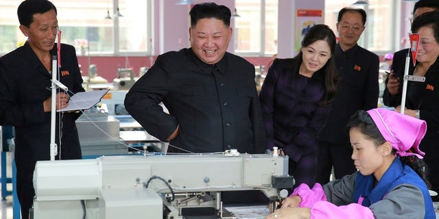 Kim and his wife at a footwear factory.