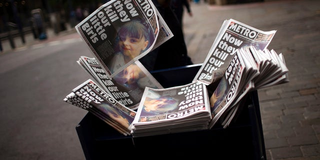 A woman grabs a newspaper reporting the news of a terror attack at Manchester Arena, May 24, 2017.