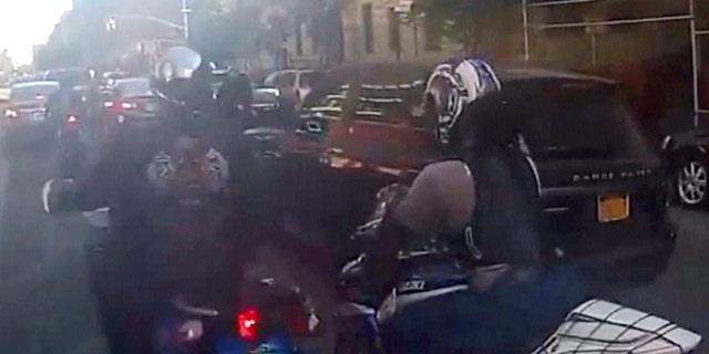 Motorcyclists ride alongside Alexian Lien's sport utility vehicle, Sunday, Sept. 29, 2013, in New York.