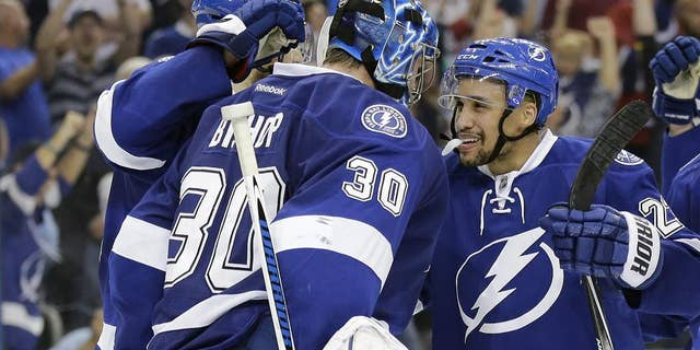 Tampa Bay Lightning goalie Ben Bishop (30) celebrates with right wing J.T. Brown (23) after the team defeated the Montreal Canadiens 4-1 during Game 6 of a second-round NHL Stanley Cup hockey playoff series Tuesday, May 12, 2015, in Tampa, Fla.  (AP Photo/Chris O'Meara)