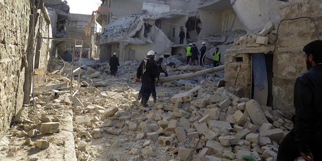 This citizen journalism image provided by Aleppo Media Center (AMC), an anti-Bashar Assad activist group which has been authenticated based on its contents and other AP reporting, shows Syrian rescue workers check the rubble of a destroyed building which was attacked by Syrian forces warplanes, in Aleppo, Syria, Tuesday, Jan. 21, 2014. (AP Photo/Aleppo Media Center, AMC)