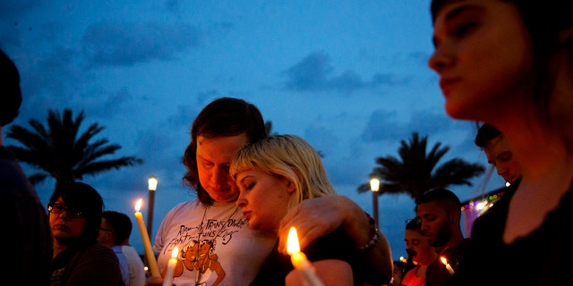 In this June 13, 2016, file photo, Lucinda Rex, right, and Clarity Thorne embrace during a candlelight vigil downtown for the victims of a mass shooting at the Pulse nightclub in Orlando, Fla.