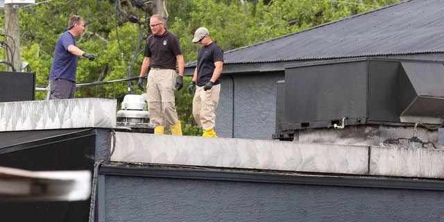 FBI lab personnel walk on the roof of the Pulse Nightclub in June.