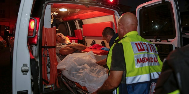 Injured person is taken to ambulance after a missile from Gaza Strip hit in the town of Sderot, Israel, Wednesday, Aug. 7, 2018.