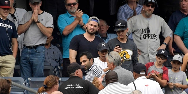 Fans react after a foul ball struck a toddler in the stands at Yankee Stadium.
