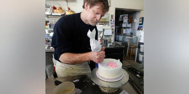 FILE - In this March 10, 2014, file photo, Masterpiece Cakeshop owner Jack Phillips decorates a cake inside his store in Lakewood, Colo.