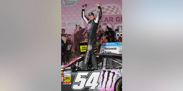 Kyle Busch celebrates in victory lane after winning the NASCAR Nationwide series auto race at Charlotte Motor Speedway in Concord, N.C., Friday, Oct. 11, 2013. (AP Photo/Chuck Burton)