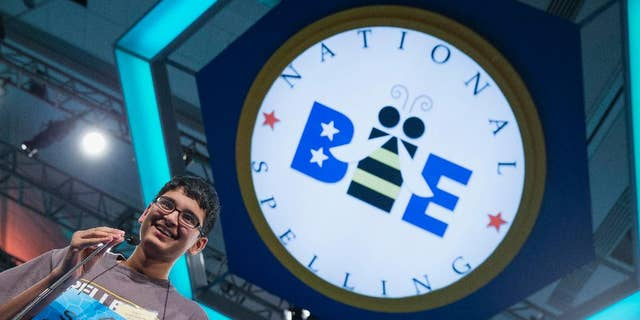 """Summedh Garimella of Duluth, Ga., smiles as he spells the word """"spelunker"""" during the preliminary round of the National Spelling Bee, Wednesday, May 28, 2014, in Oxon Hill, Md. (AP Photo/ Evan Vucci)"""