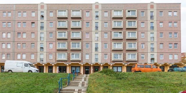 """An apartment block photographed  in Schmoelln, eastern Germany, Sunday Oct. 23, 2016.  Officers were called to this building in Schmoelln on Friday afternoon  Oct. 21, 2016 by the caregiver for a group of young migrants, who reported that a 17-year-old Somali boy was acting violently, police said. When they arrived, he was sitting on a fifth-floor window ledge. Police and fire officers tried to persuade the teenager not to jump, but he leapt and died shortly afterward of his injuries.   Onlookers apparently shouted """"Jump!"""" before the  teenage migrant leapt from the  apartment block in the  eastern German town, suffering fatal injuries, the mayor said Saturday Oct. 22, 2016 .  (Michael Reichel/dpa via AP)"""