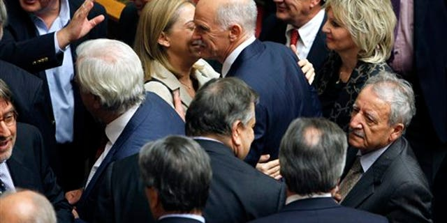 Nov. 5, 2011: Greek Prime Minister George Papandreou, center, is congratulated by his party's ministers and lawmakers after surviving a confidence vote.