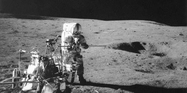 Apollo 14 astronaut Alan B. Shepard Jr. conducts an experiment near a lunar crater.