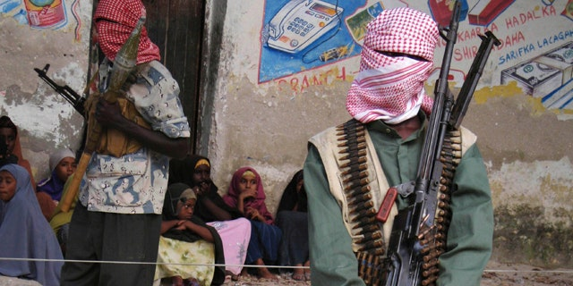 Dec. 18, 2008: Somali al-Shabab fighters stand stand guard during a public flogging by the hardline Islamic group in Bula Marer town.