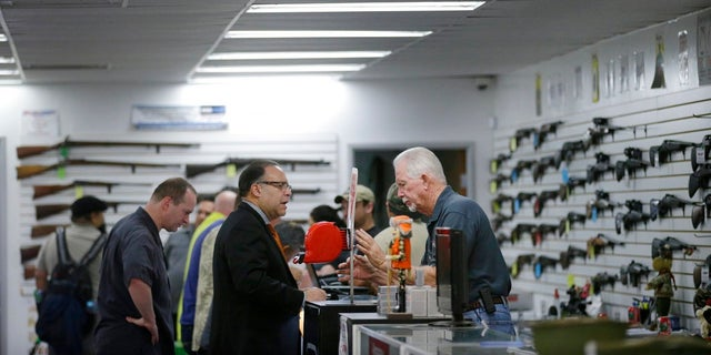n this Dec. 9, 2015, file photo, sales associate Mike Conway, right, shows Paul Angulo a pistol at Bullseye Sport gun shop in Riverside, Calif. A U.S. judge has struck down a nearly century-old California law that banned gun shops from advertising handguns on their premises.