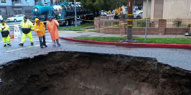 Inspectors examine a sinkhole Saturday, Feb. 18, 2017, in Studio City, north of Los Angeles. Two vehicles fell into the 20-foot sinkhole on Friday night and firefighters had to rescue one woman who escaped her car but was found standing on her overturned vehicle.  (AP Photo/Ringo H.W. Chiu)