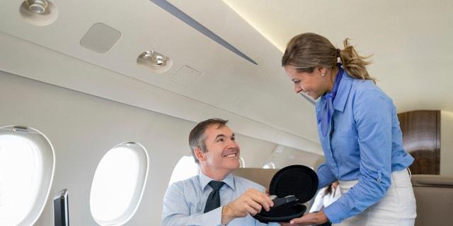 Friendly first class flight attendant serving a passenger in an airplane handling headphones