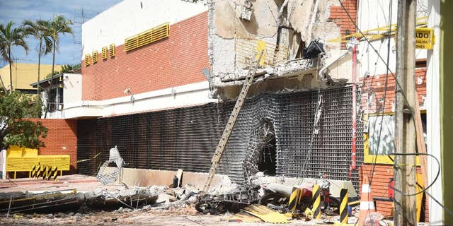"""The partly demolished building of the armored car company Prosegur is seen after assailants blew it up, in Ciudad del Este, Paraguay, Monday, April 24, 2017. A gang of over 50 armed bandits stole several million dollars from a vault in the company, in what local officials are dubbing the """"robbery of the century"""". The culprits, who police said were from Brazil, killed one police officer during the Monday raid. (Roberto Zarza/Diario ABC Color via AP)"""
