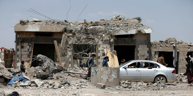 People walk to the site after a Saudi-led coalition airstrike in Arhab area, north of Sana'a, Yemen in August 2017
