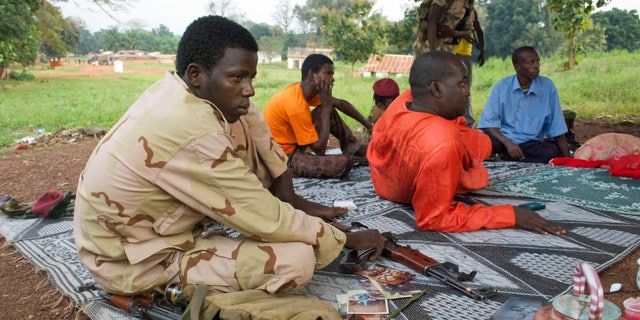 """In this photo taken Monday, Nov. 25, 2013, armed Muslim fighters from the former Seleka rebel coalition sit in the town of Bouca in the Central African Republic. France's foreign minister has warned that its former colony in central Africa is """"on the verge of genocide"""" as attacks mount across the country's remote northwest between the mostly Muslim fighters of the Seleka rebel coalition who ousted the president in March, and """"anti-balaka"""" Christian militias that have emerged to defend towns and in some cases attack Muslim civilian communities. (AP Photo/Florence Richard)"""
