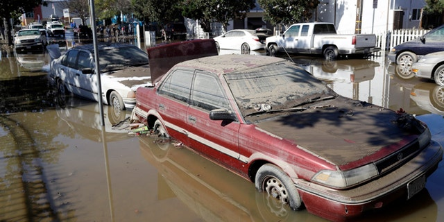 FILE - In this Feb. 23, 2017, file photo, cars are partially submerged and covered in mud from receding floodwaters in San Jose, Calif. California billionaire Kieu Hoang donated $5 million to flood relief efforts on March 1, 2017. (AP Photo/Marcio Jose Sanchez, File)