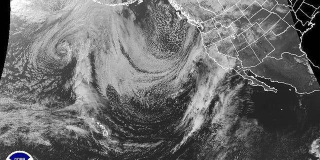 """This March 21, 2018 satellite image provided by the National Oceanic and Atmospheric Administration shows a strong Pacific storm, known as a """"Pineapple Express,"""" the lower arc of clouds that range from Hawaii at lower left, aimed directly at California, middle right, that dropped heavy rain on a wide swath of the state."""