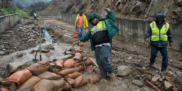 Workers place sandbags on a washed-out driveway on La Tuna Canyon Road in Sun Valley, Calif.